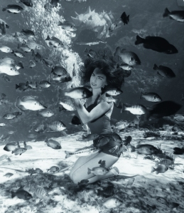 The first Weeki Wachee Mermaids did not wear tails or any other costumes. Here, Bonnie Georgiadis feeds the fish, a standard act in the shows. 1967.