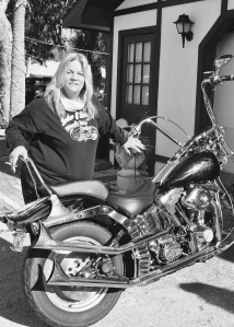 "From Ch. 3 ""Sisters of Steel."" Leather & Lace MC Founder and president Jennifer Chaffin takes a break from overseeing her club's weeklong gathering to show her bike."