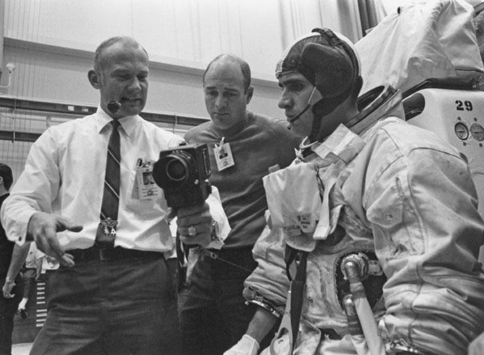 "Aldrin (left) meets with astronauts Ron Evans (center) and Schmitt during a lunar surface experiment deployment simulation on January 21. Aldrin examines a Hasselblad 500 EL Data Camera similar to one he would use on the lunar surface. Evans was a member of the Apollo 11 astronaut ""third string"" support crew. (NASA)"
