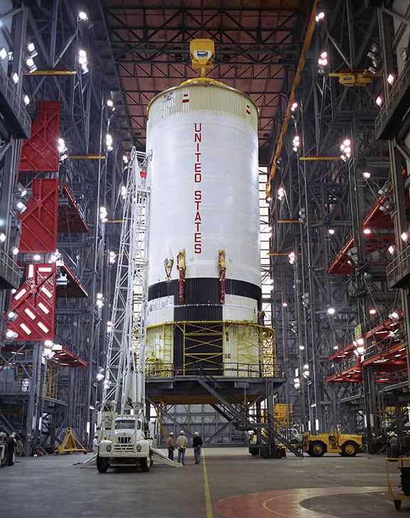 A crane prepares to lift Apollo 11's S-II booster off a workstand in the transfer aisle of the VAB on February 6, 1969. The 81.5-foot-tall and 33-foot-diameter S-II was built by North American Rockwell in Seal Beach, California, and, powered by five J-2 engines, produced approximately 1,000,000 pounds of thrust. (NASA)