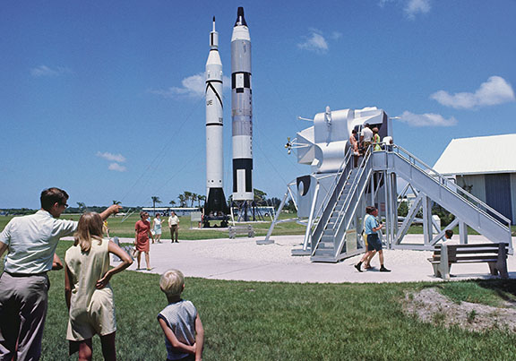 "Tourists take in the rocket and spacecraft display at KSC Visitor Center. ""Apollo fever"" was gripping the country as KSC became the focal point for the upcoming Moon launch. More than 8,000 people were touring the Moonport daily in the week leading up to the launch. (Photo by Tiziou News Service)"