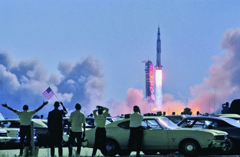 Spectators in a parking lot near the VAB wave an American flag as Apollo 11 begins its journey to the Moon. The Saturn's automatic engine shutdown function was inhibited during the first thirty seconds to prevent the vehicle from falling back onto the pad during a launch failure, seen as the least preferable option at that stage of the flight. (Photo by Tiziou News Service)