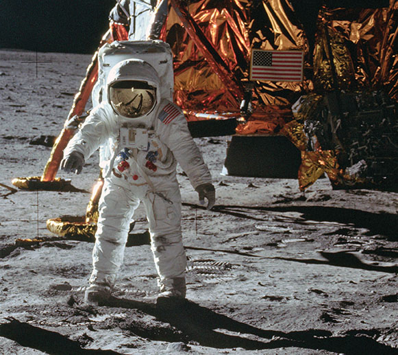 Aldrin with the LM behind him shortly after he has deployed the SWC. If the photo is enlarged, Armstrong can be seen reflected in Aldrin's visor. Visible on the front of Aldrin's suit are his PLSS Remote Control Unit and camera bracket. (NASA)