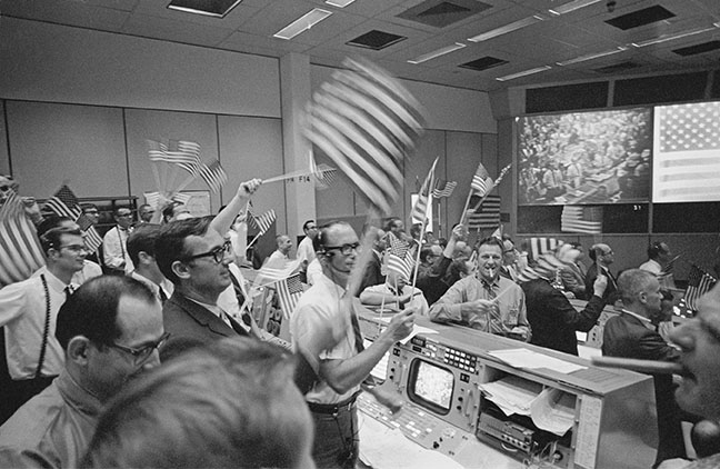 Members of the flight control team at Mission Control in Houston wave U.S. flags and light up cigars at the successful conclusion of the mission on July 24. (NASA)